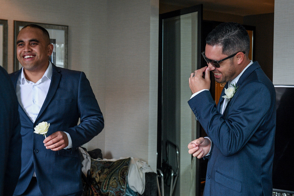 Groom and groomsmen share a laugh during wedding prep