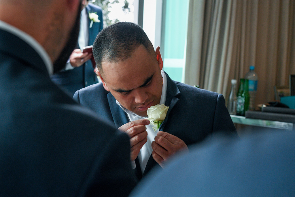 The groom adjusts his boutonniere at wedding prep