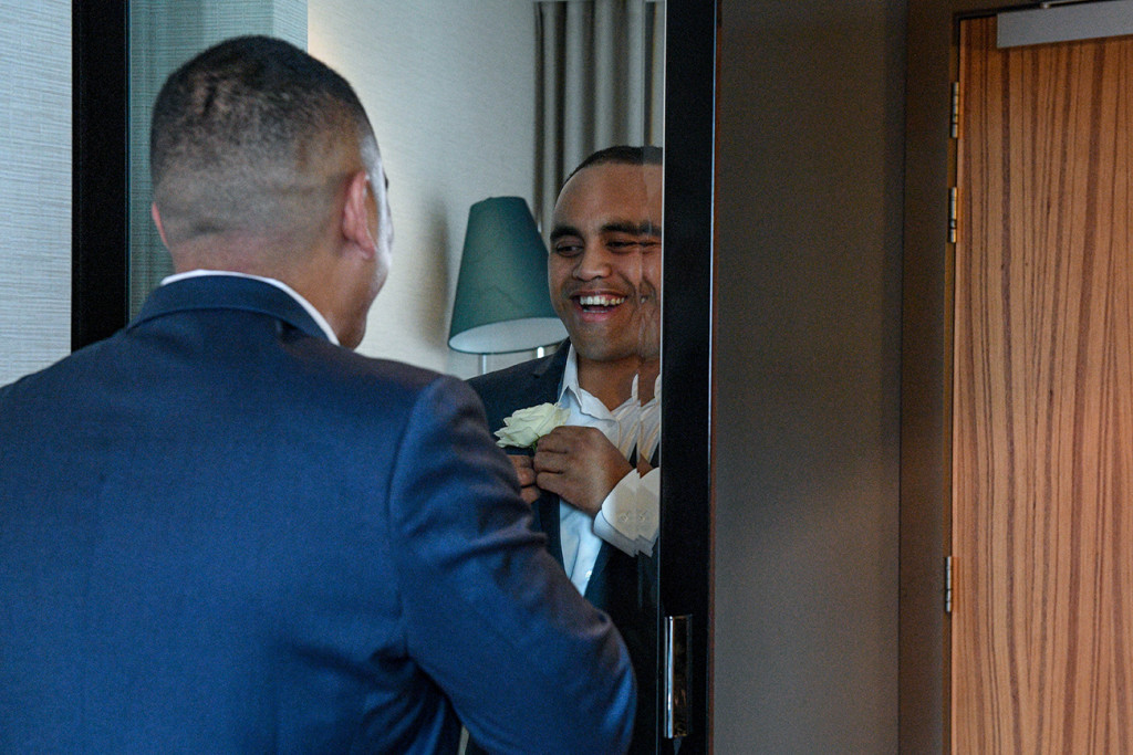 Groom smiles at mirror while adjusting his boutonniere