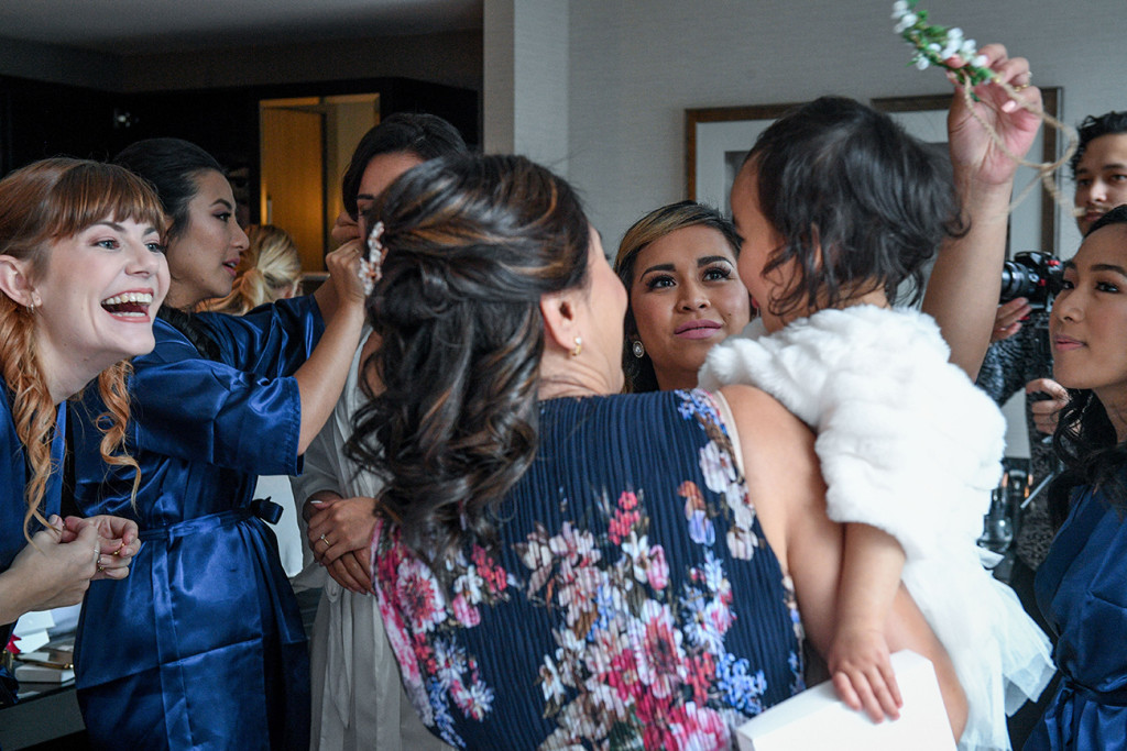 Bridesmaids play around with the bride's daughter during wedding preparation