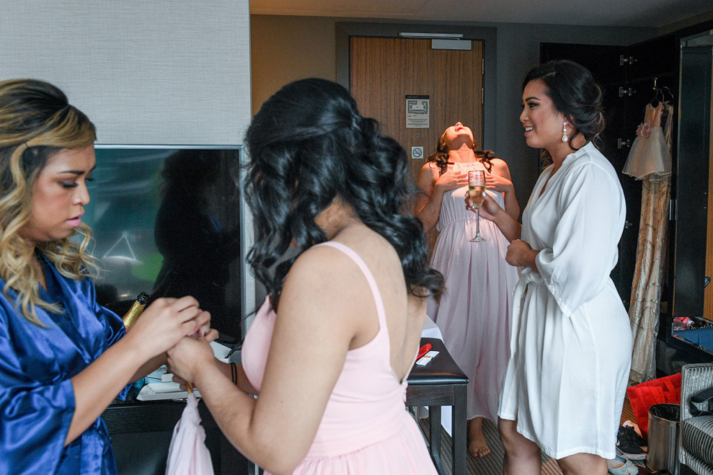 Bridesmaids drink champagne as they have their makeup done