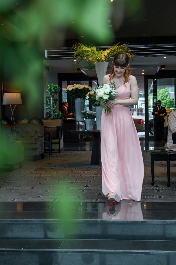 Bridesmaid walks down the aisle at the Sofitel Auckland