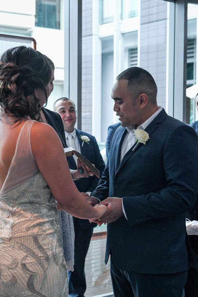 Groom holds brides hands as he says his vows