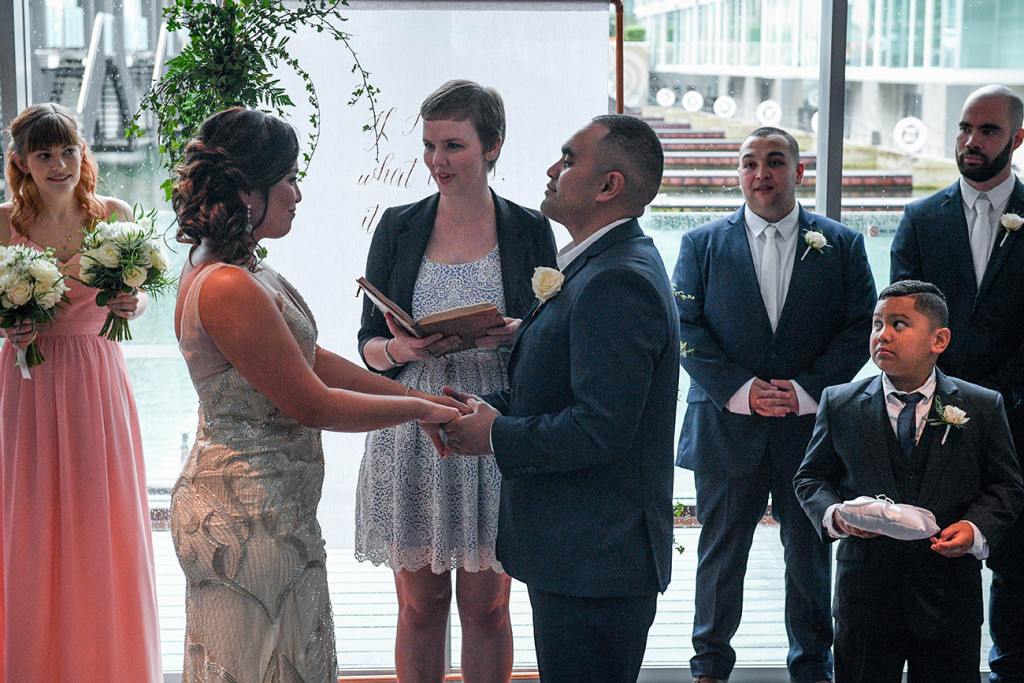 Bride and groom hold hands at the Sofitel Auckland as they exchange vows