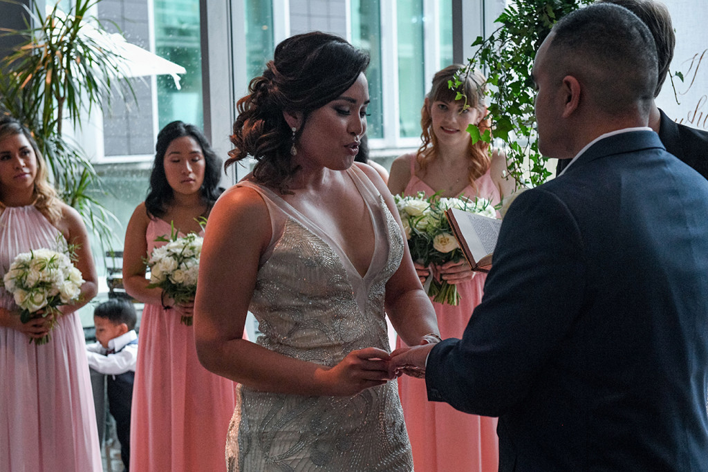 Bride holds grooms hand as she says her vows