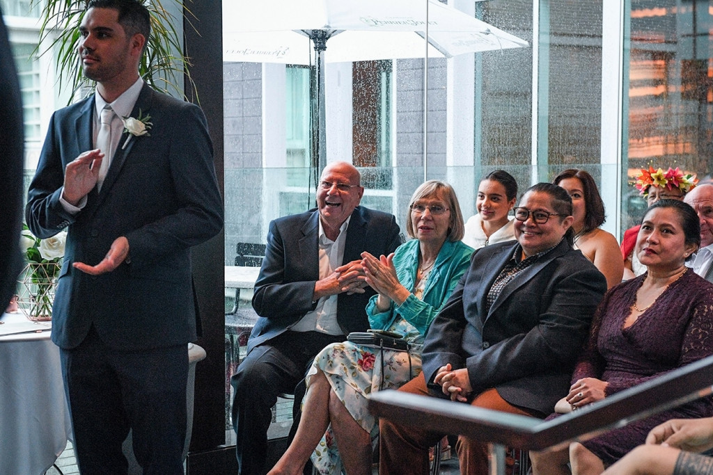 Wedding guests look on as bride and groom exchange vows