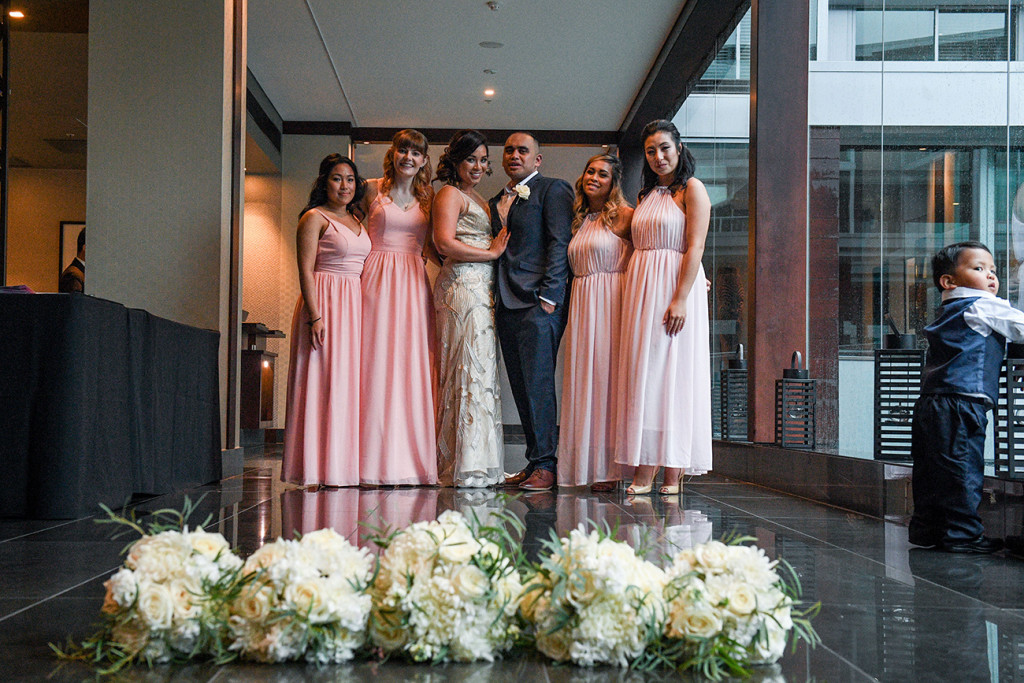 Bride, groom and bridesmaids in pink with white flower bouquet
