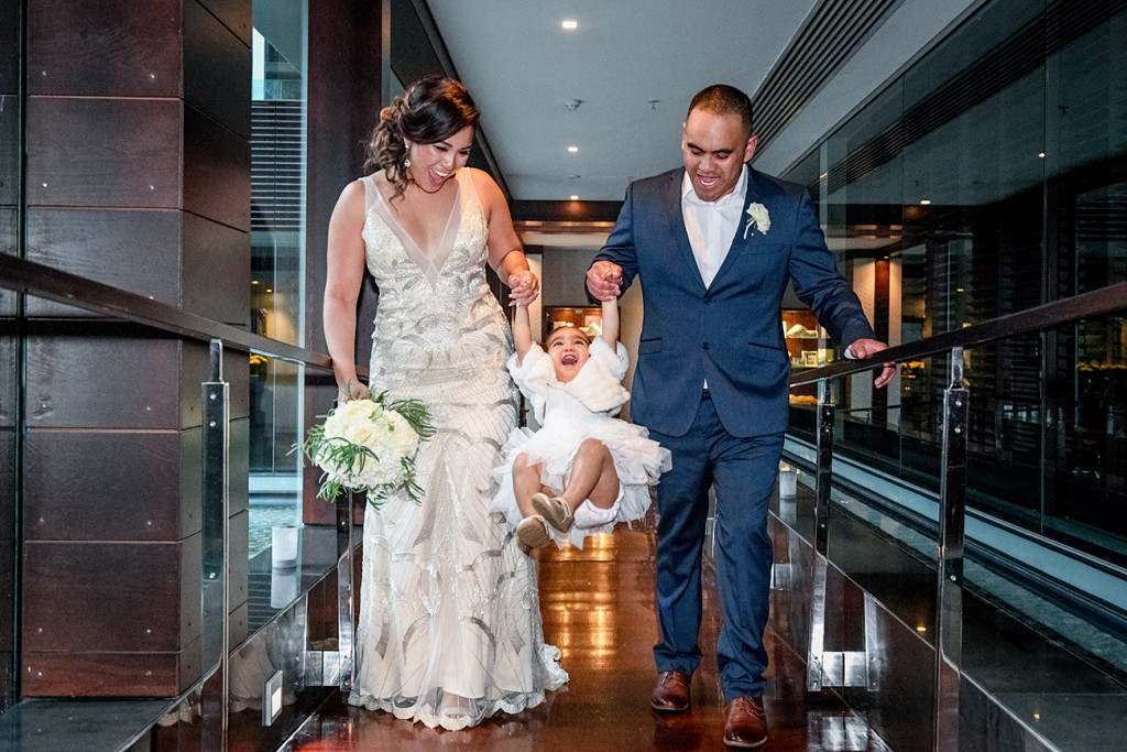 Bride and groom lift their daughter up at the Sofitel Auckland