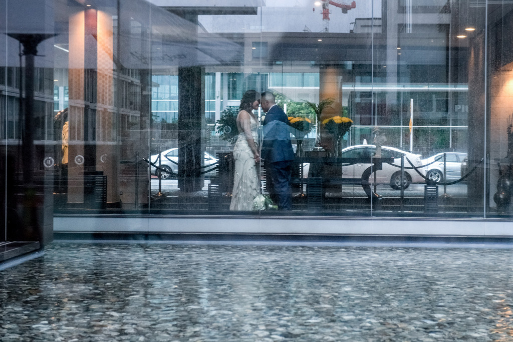 Wideshot through a glass wall of the bride and groom kissing