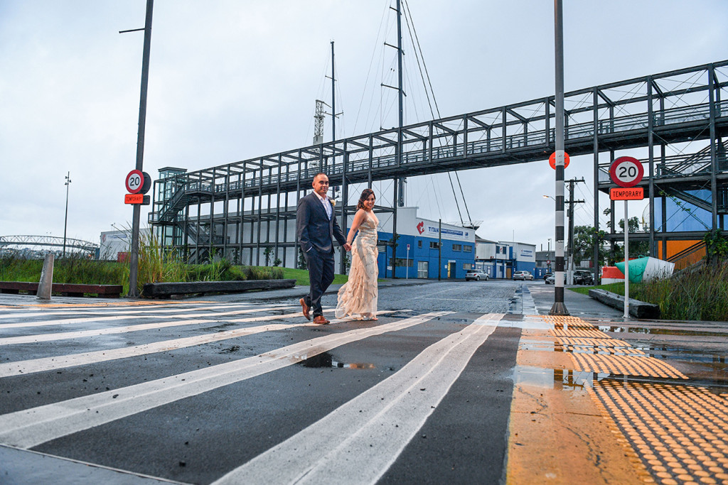 Bride and groom cross the street in wet Auckland streets