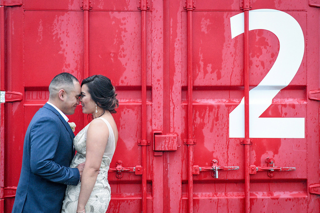 Bride and groom against red container at the Auckland Viaduct