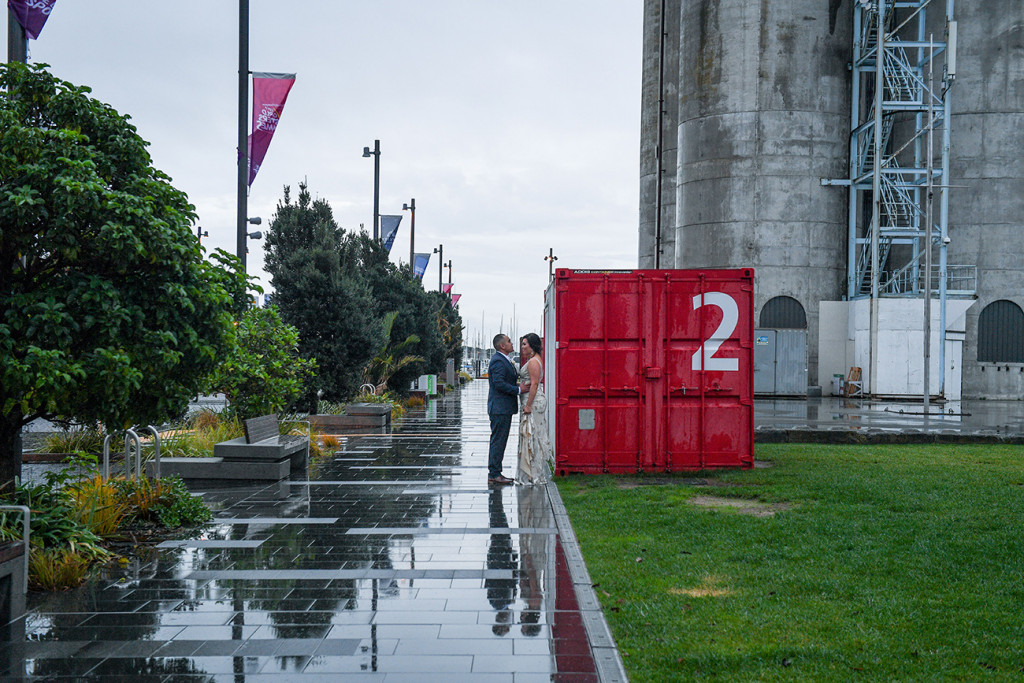 Bride and groom against red container at Auckland's viaduct