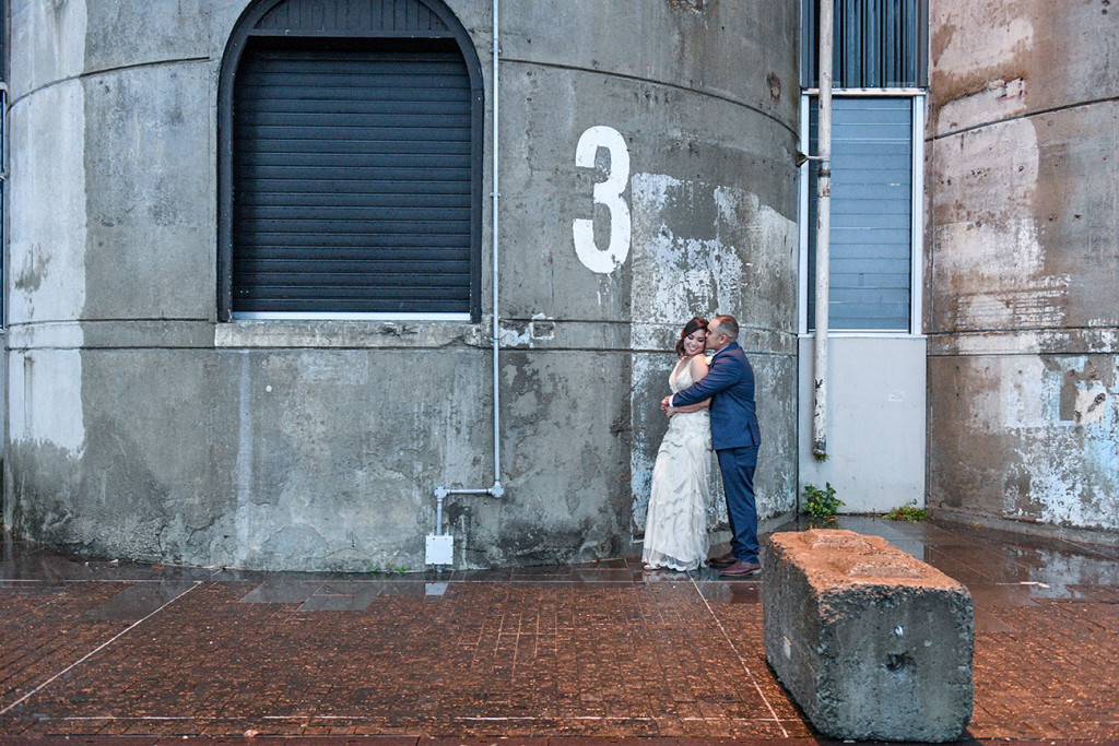 Bride and groom against grey wall in Auckland city wedding photo shoot