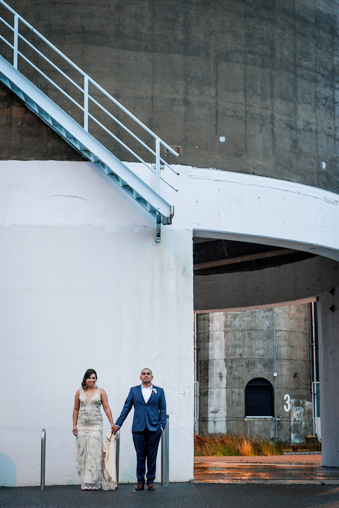 Stunning wideshot of bride and groom against wall in Auckland wedding shoot