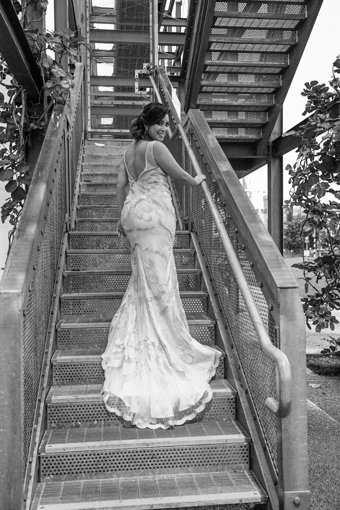 Monochrome photo of bride walking up steps