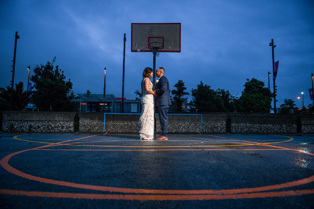Bride and groom dance on Auckland basketball court at night