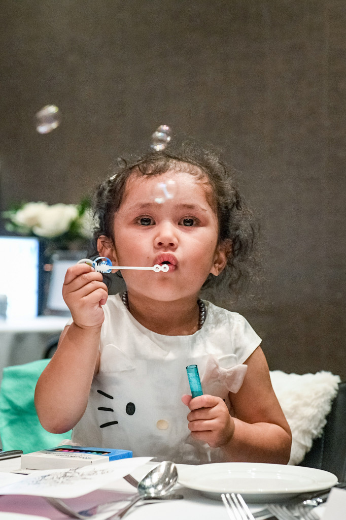 Bride's daughter blows bubbles at the wedding reception