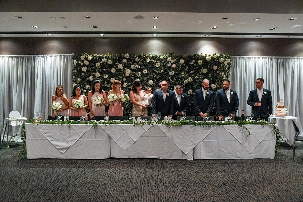 Bridesmaids and groomsmen stand at the reception