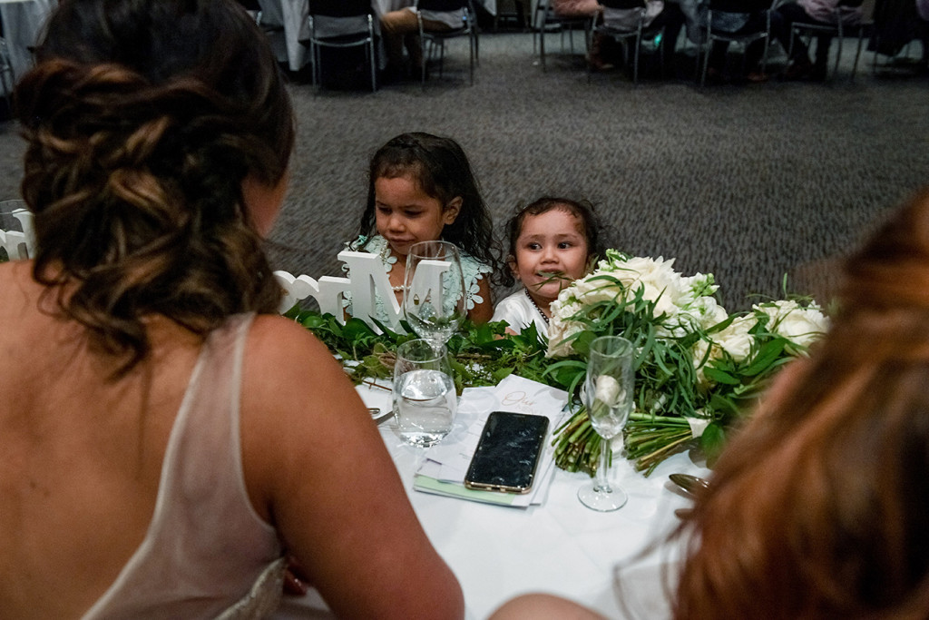 Flowergirls peek from ontop of the table and laugh at the bridal party