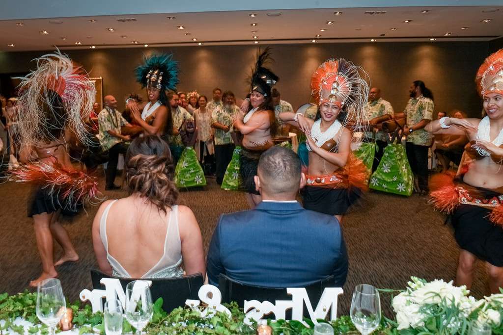 Bride and groom watch traditional Polynesian dance