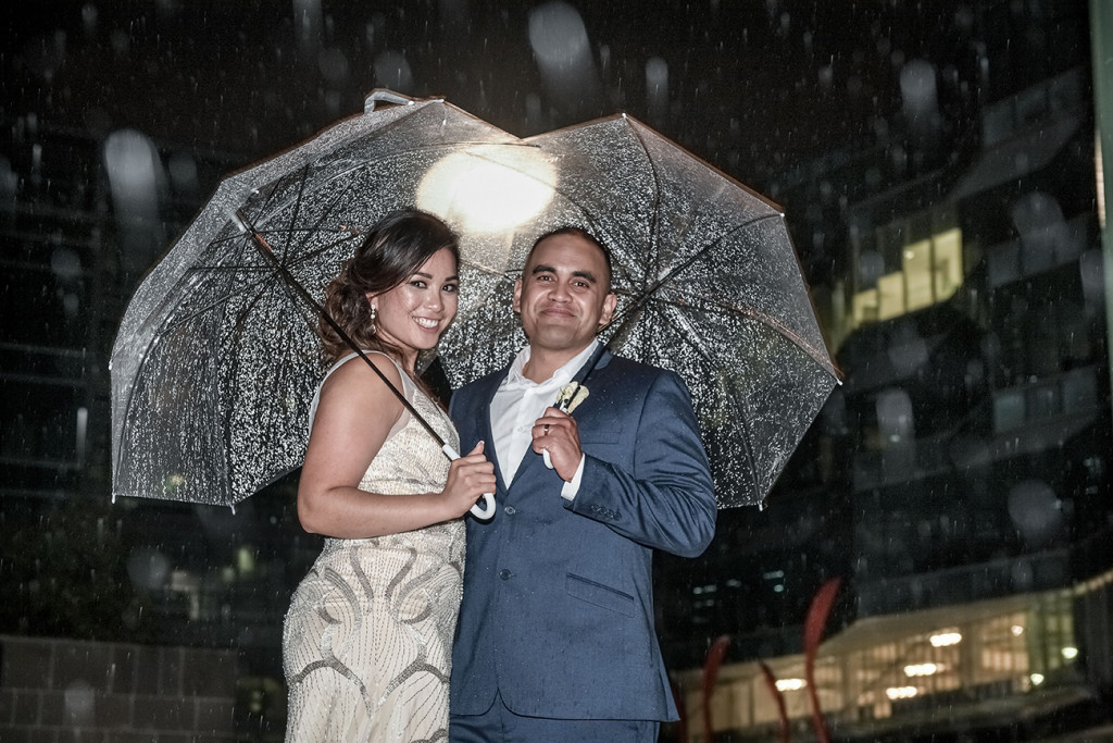 Bride and groom pose with umbrellas in the rain at night at the Viaduct