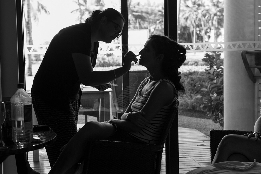 Silhouette photo of bride's make up being touched up.