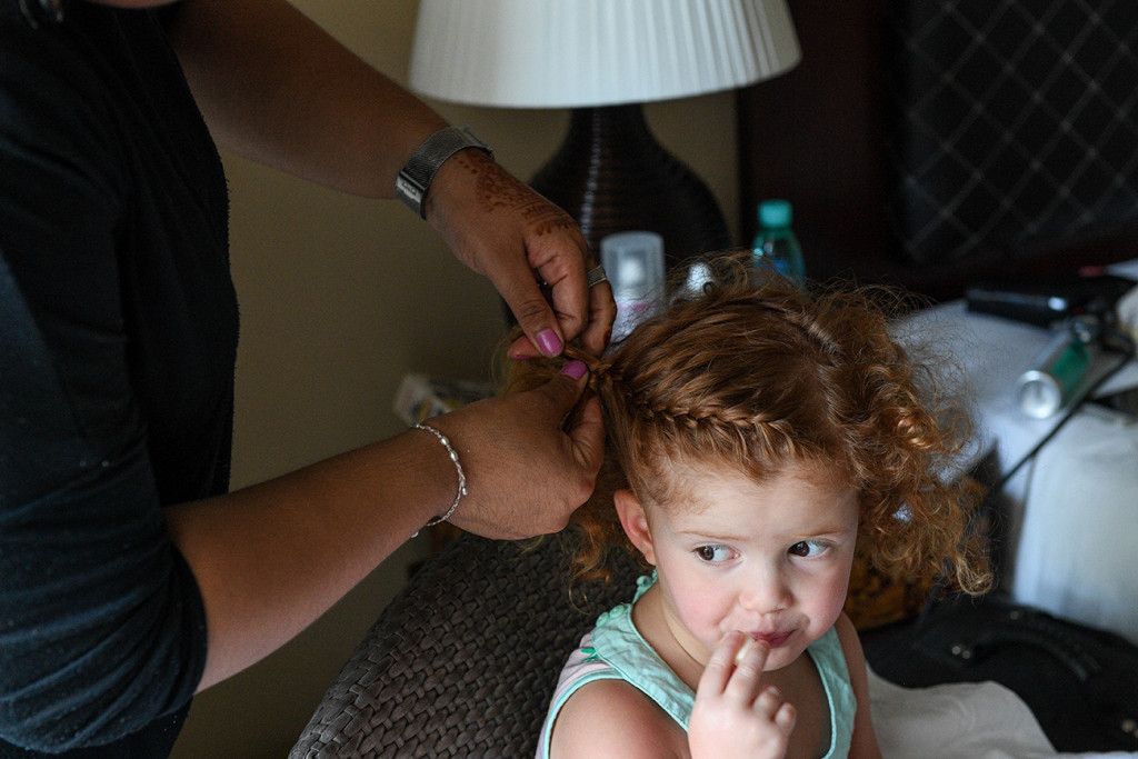 Flower girl gets a french plait in her hair during wedding preparations
