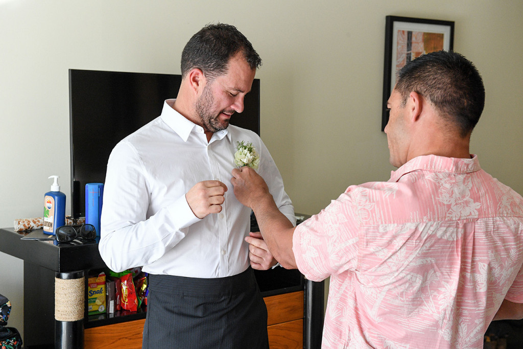 Groomsman helps groom with boutonniere