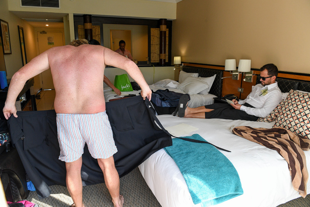 Half naked groomsman gets ready during wedding day preparation