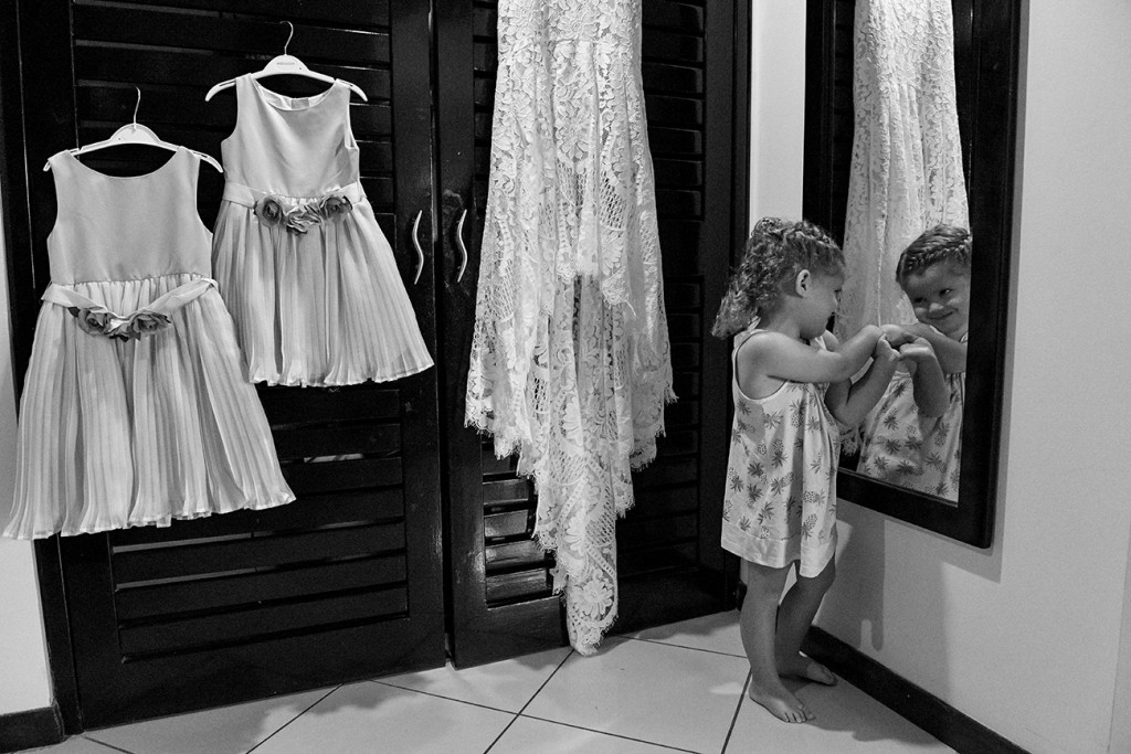 Black and white photo of bride's lace wedding dress and flower girls dress hanging