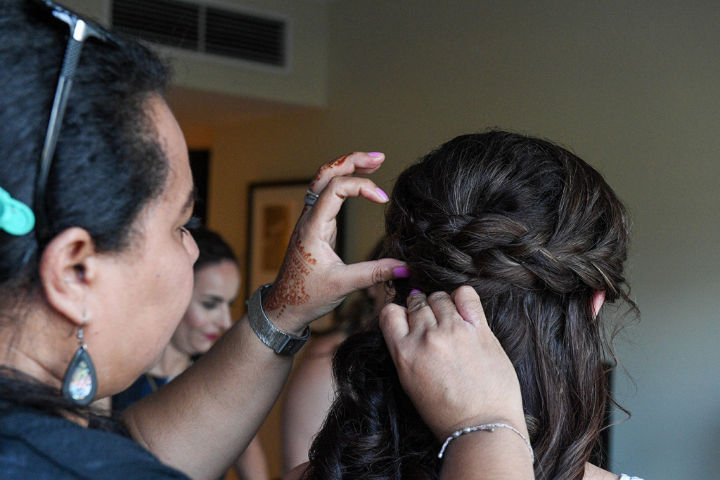 Bride's hair being plaited during wedding preparations