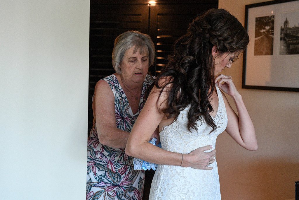 Mom helps bride tie up the back of her wedding dress at Sofitel Fiji wedding