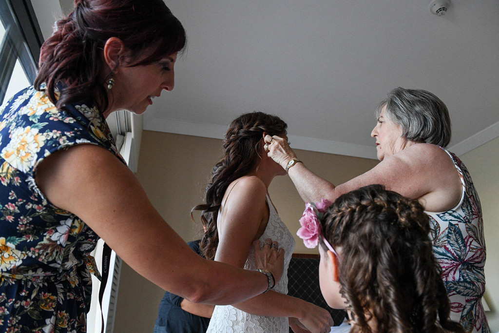 Mom puts hair brooch in brides hair during preparation
