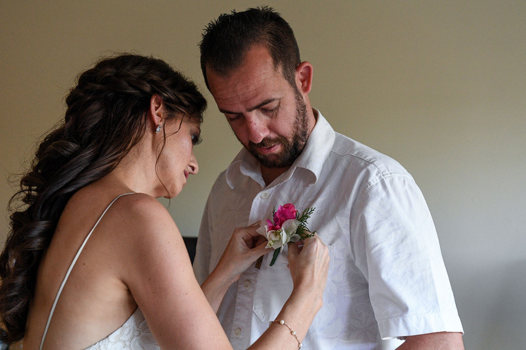 Bride helps groom put on boutonniere