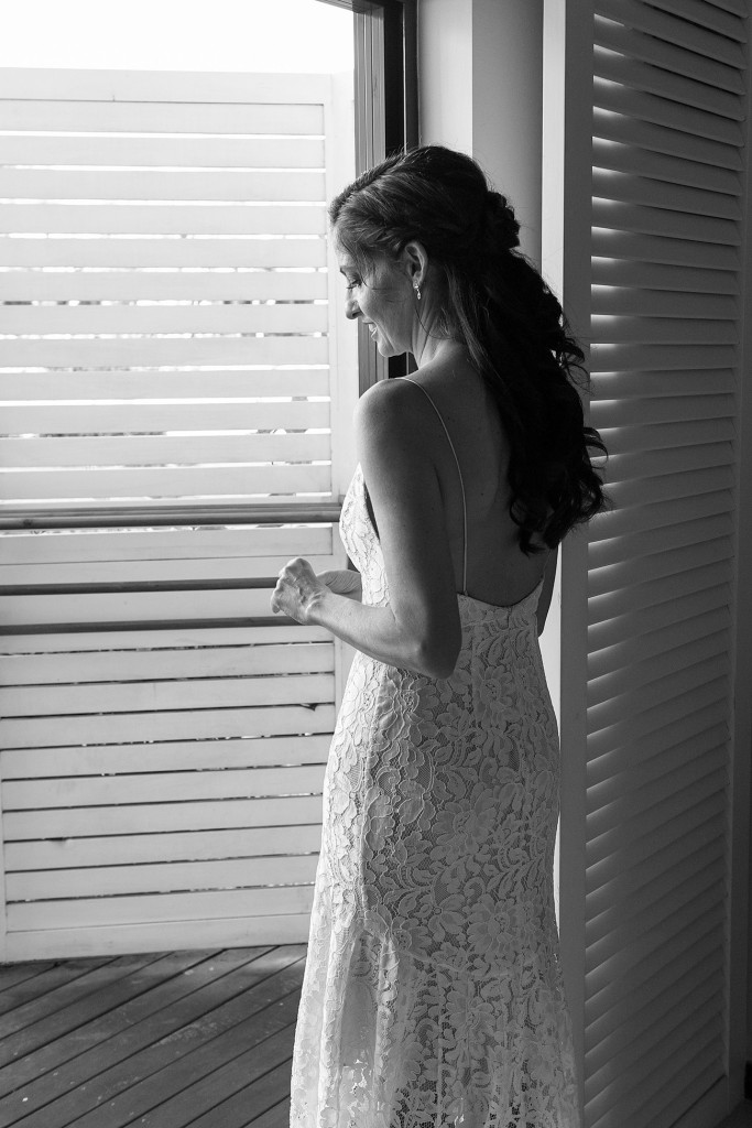 Stunning black and white photo of bride looking out of louvered window