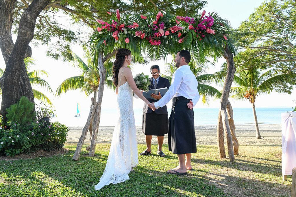 Wideshot of bride and groom saying vows at beachside wedding in Sofitel Fiji
