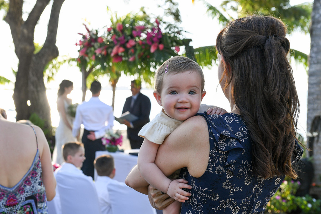 Cute baby smiles at camera in outdoor Fiji Sofitel Wedding