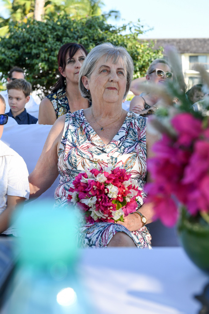 Bride's mom watches couple exchanging vows at the altar