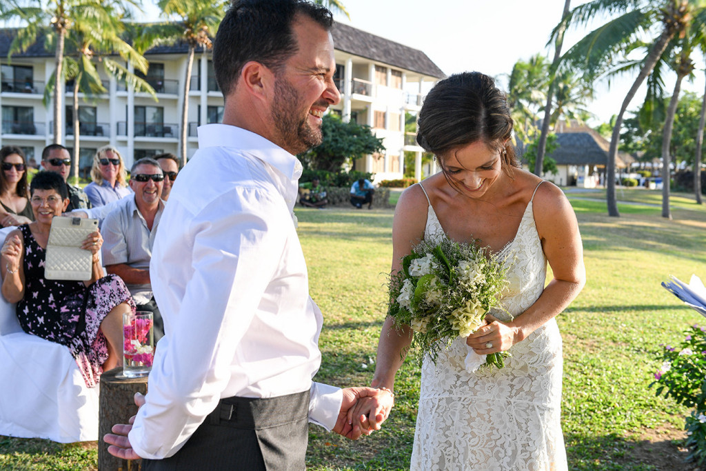 Stunning bride laughs with groom at the altar at beachside wedding Fiji