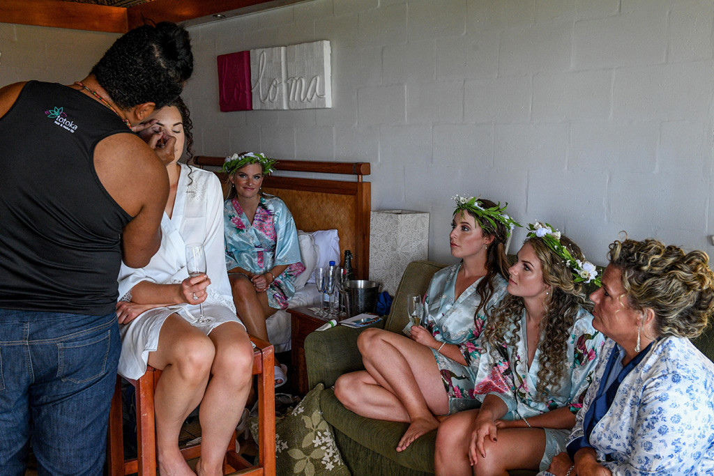 Bridesmaids watch as bride's makeup is done by Totoka Hair and Makeup
