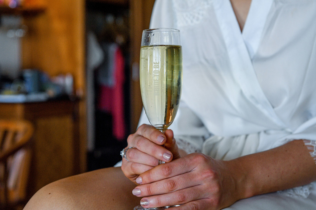 Champagne flute held by bride at boho wedding