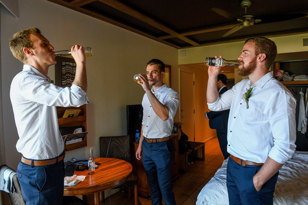 Groom and groomsmen sharing a cheeky beer before the wedding