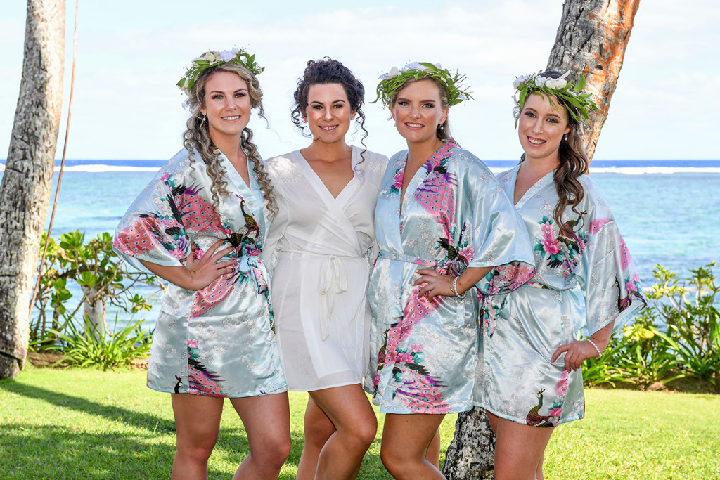 Bride poses with bridesmaids dressed in blue floral dressing gowns by the beach