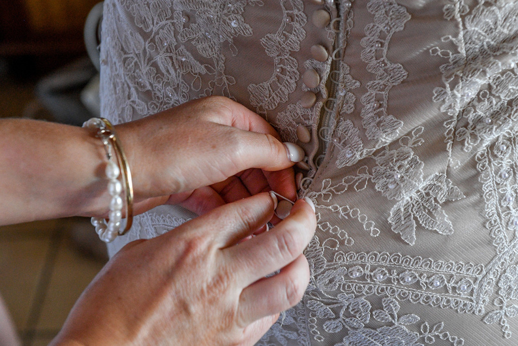 Close up detail of bride zipping up lace and pearls wedding dress