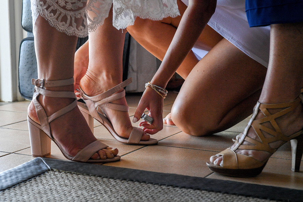 Closeup of bride slipping on beige heels