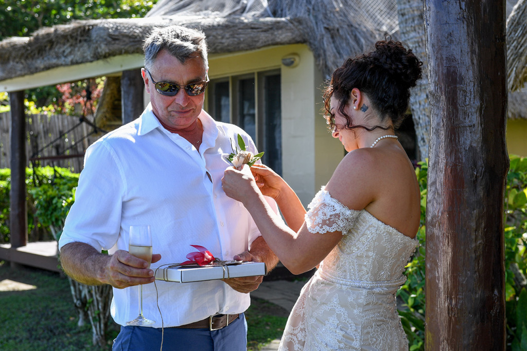 Bride adjusts boutonniere on her dad's shirt in Fiji wedding