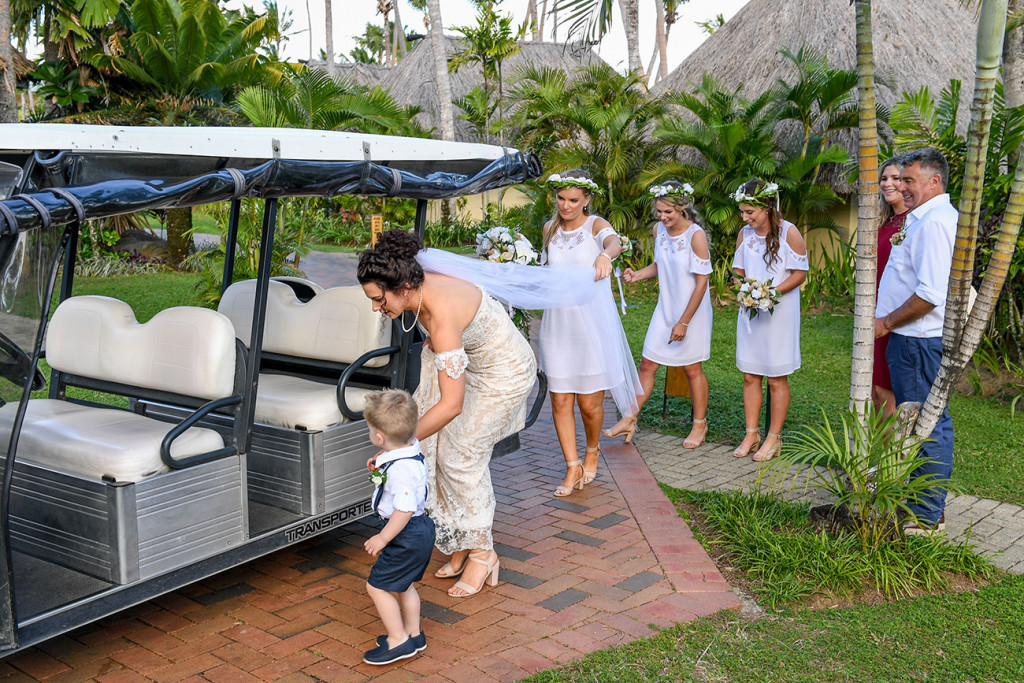 Bride getting into golf cart with bridesmaids