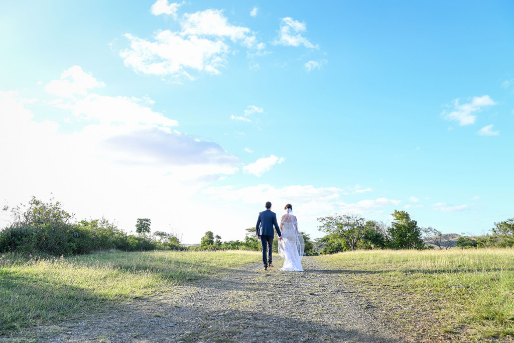 Wideshot of Bride and groom walking into Fiji Greenery