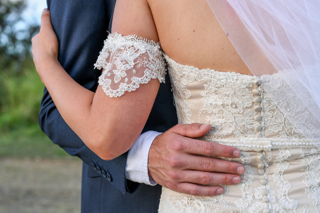 Closeup of grooms hand on bride's hips