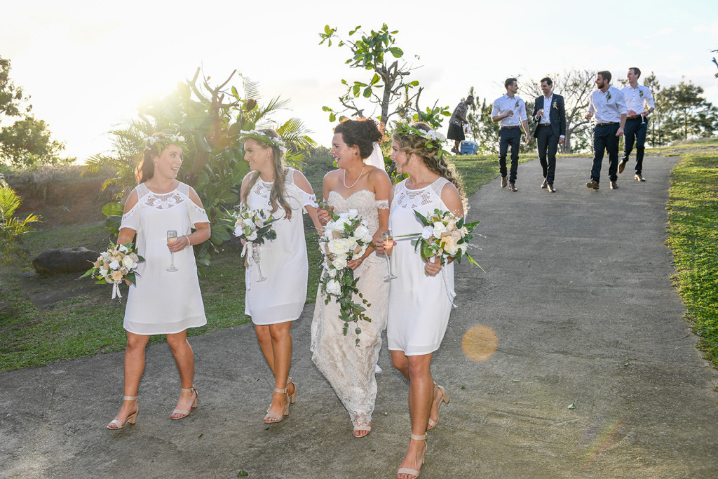 Bohemian bride and bridesmaids walk down hill in Outrigger Fiji